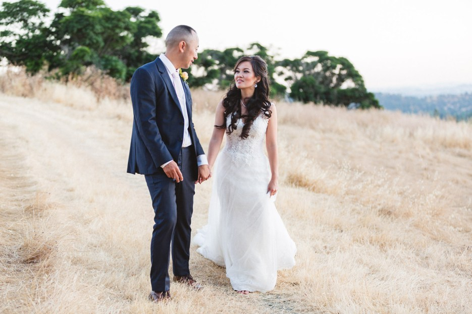marrying couple walking in dry grass at intimate bay area wedding