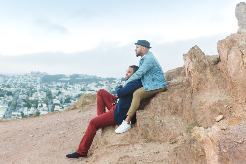 engaged couple surveys view of san francisco from corona heights rocks