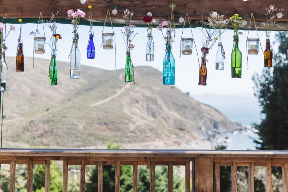 elegant wedding display of hanging bottles overlooking pacific ocean