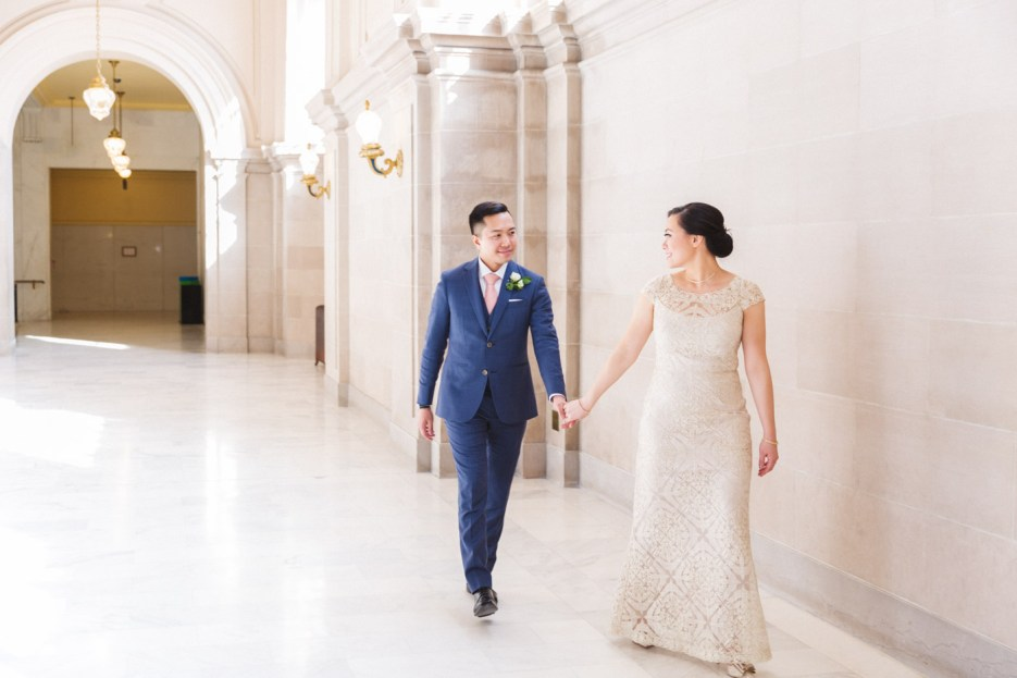 bride leads groom by the hand in airy san francisco city hall corridor