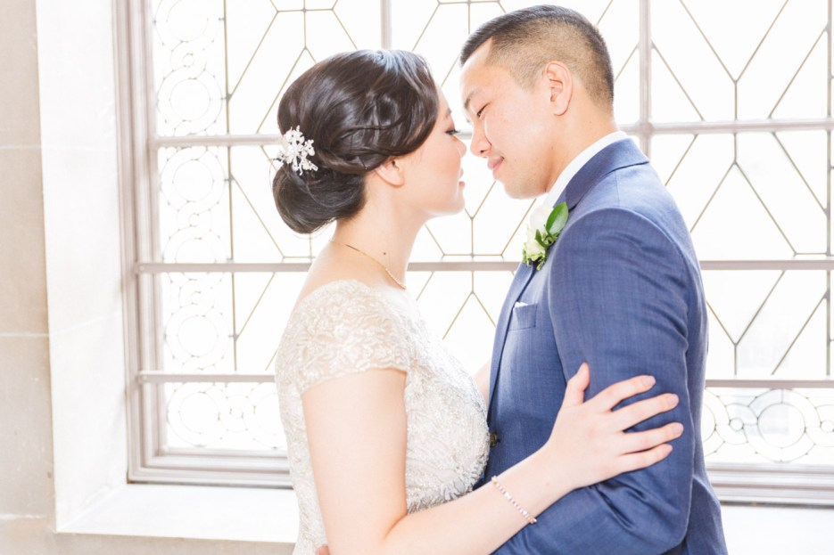bride and groom go in for kiss by window city hall wedding