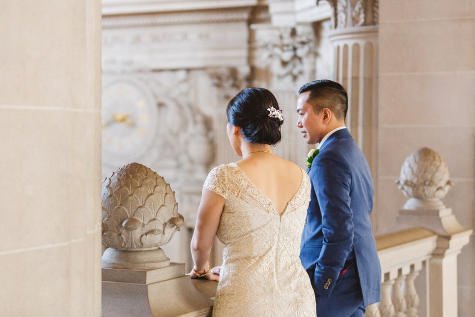 bride and groom look down at staircase