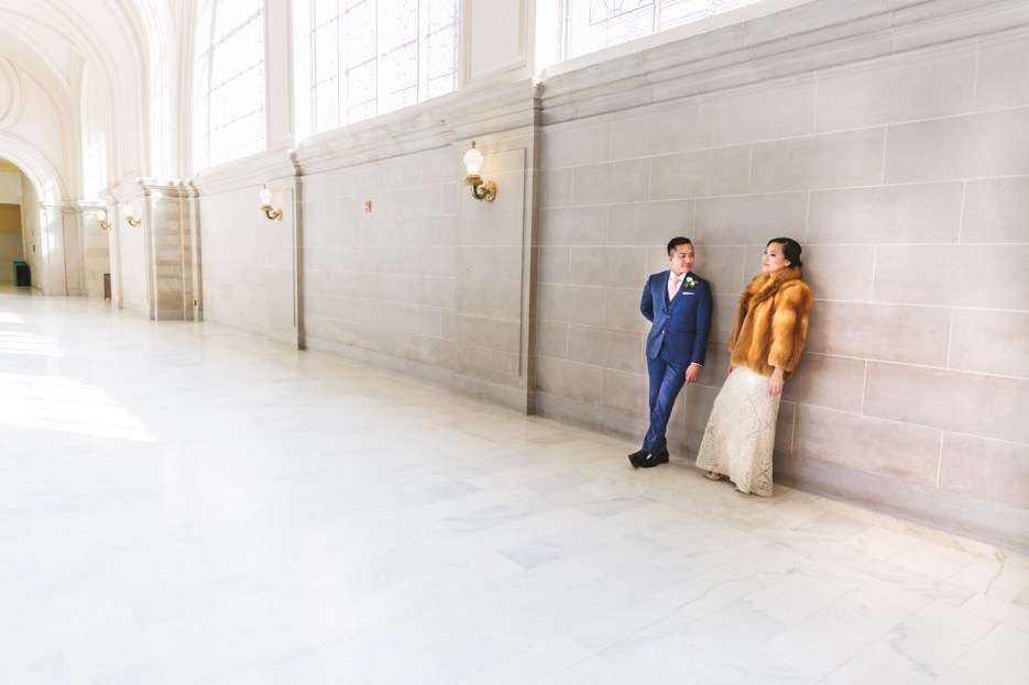 bride in fur coat and groom seem small in grand city hall