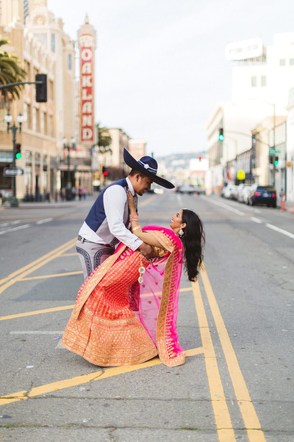 downtown oakland engagement photography man dips woman in cultural dress