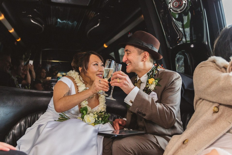 san francisco wedding couple cheers in back of limo after their San Francisco City Hall wedding