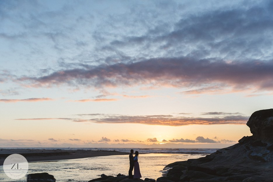 silhouette of couple on beach at engagement shoot