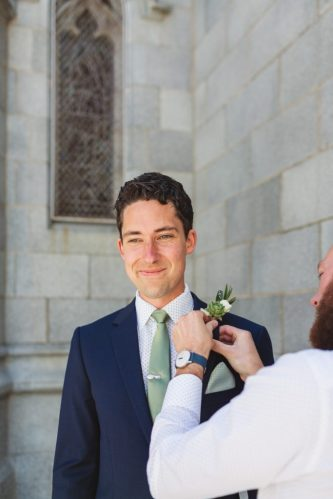 groom's boutonniere being pinned on