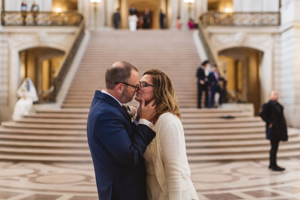 couple kissing at the bottom of grand staircase city hall