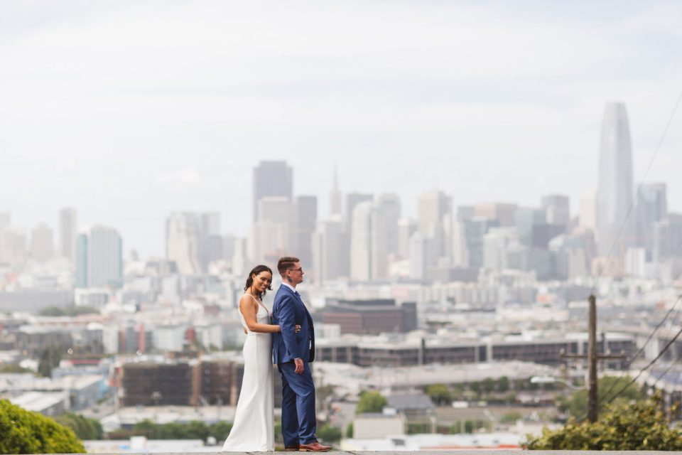 Bride and groom posing with san francisco skyline at Potrero Hill Wisconsin & 20th Streets after city hall wedding