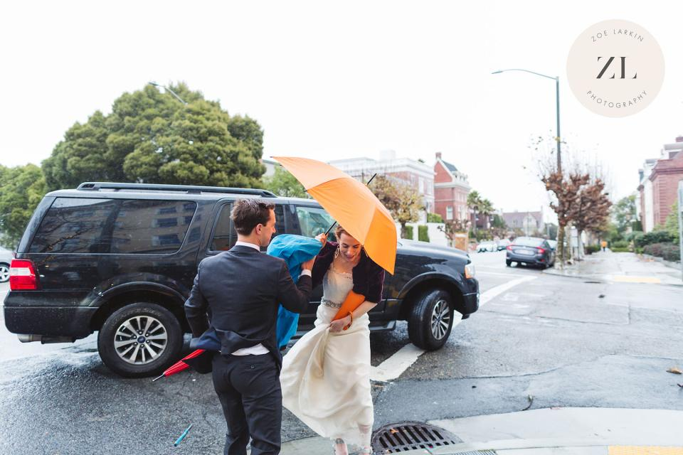 bride with umbrella exiting hired car on san Francisco city hall wedding day