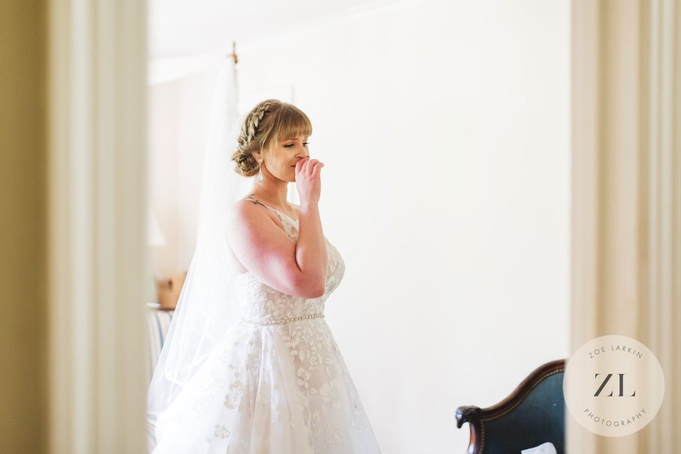 tearful bride looking at herself in mirror at the Monte Verde Inn, Foresthill wedding venue