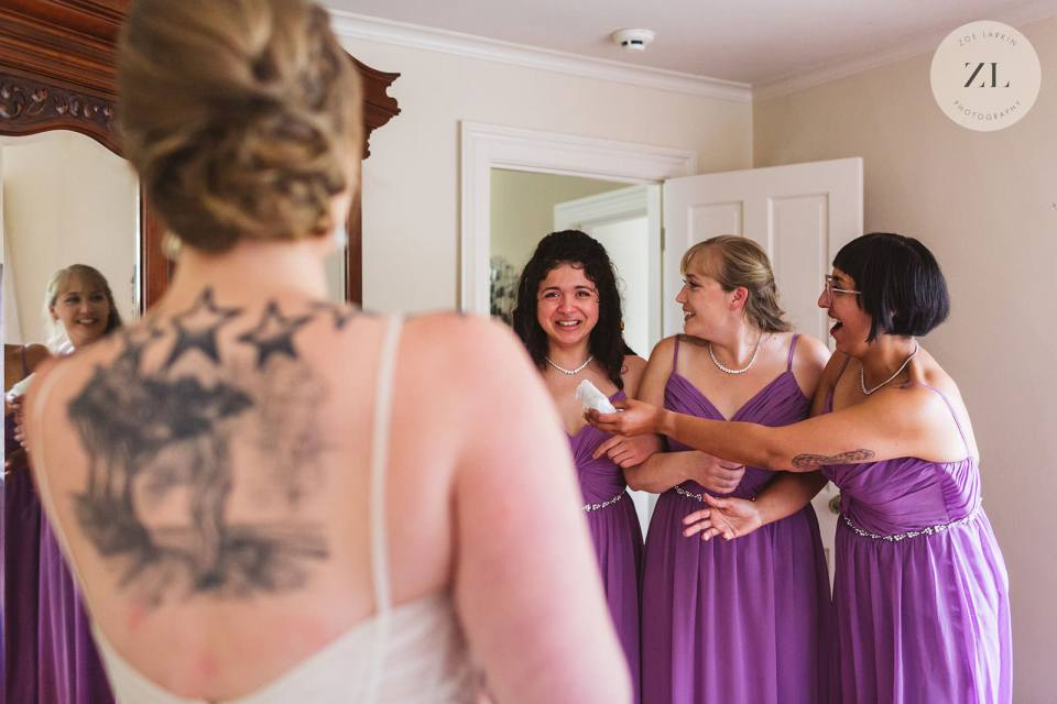 candid photo of bridesmaids first look - the questions to ask wedding photographer