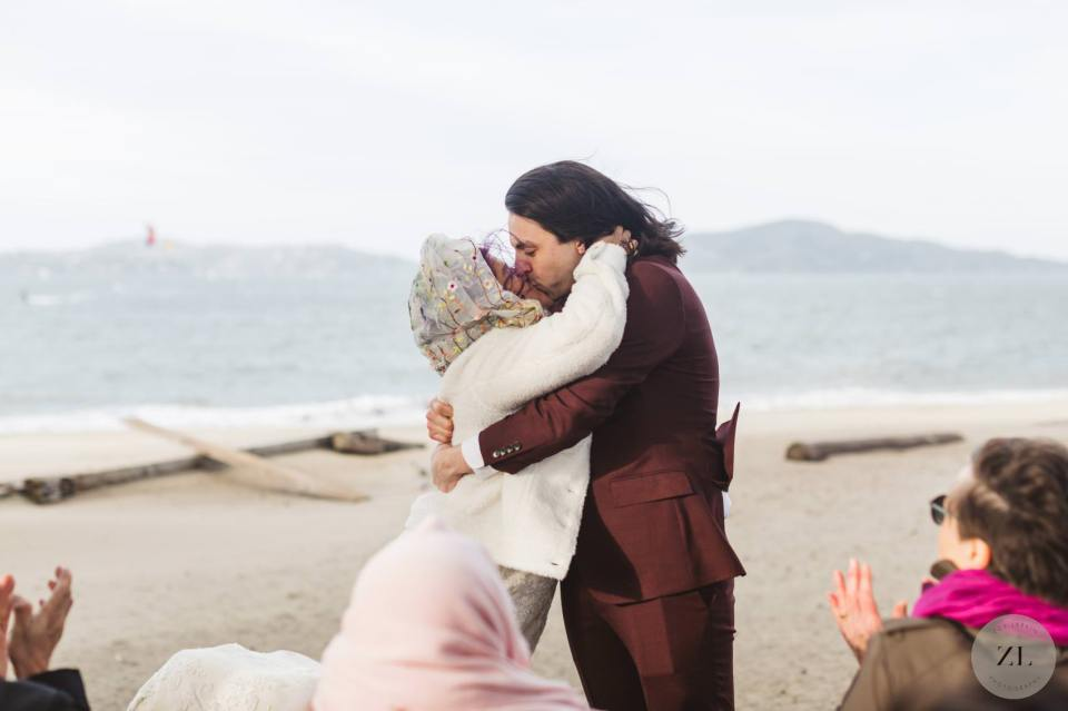 wedding couple's first kiss at Crissy Field beach Cypress Grove