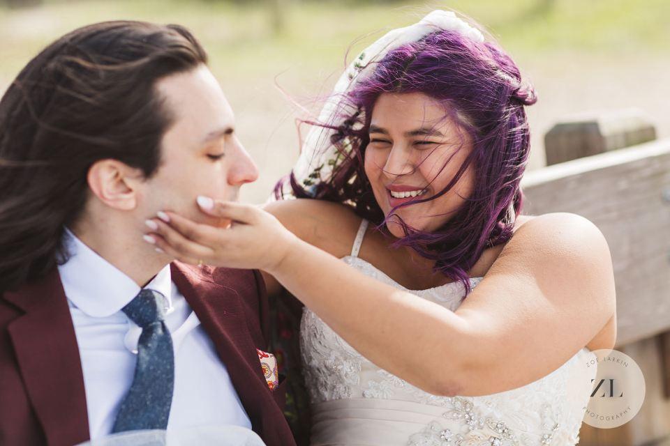 Bride caressing groom on intimate wedding day at san francisco beach wedding