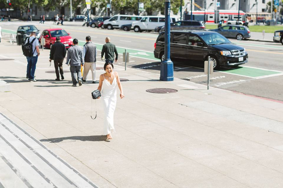 Many things that wedding clients should realize about how to make your wedding photographer really happy so they can do great work - be on time! Image showing bride giggling as she arrives at San Francisco City Hall