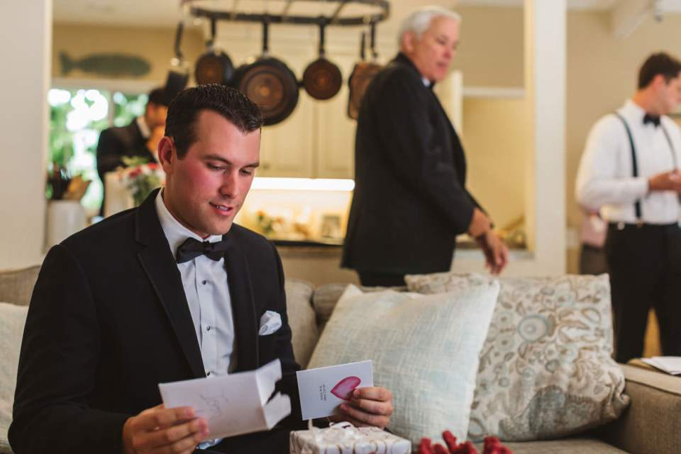 Ways to be a great bride so your wedding photographer can do their best work at your wedding! Image showing groom opening a card from his bride-to-be