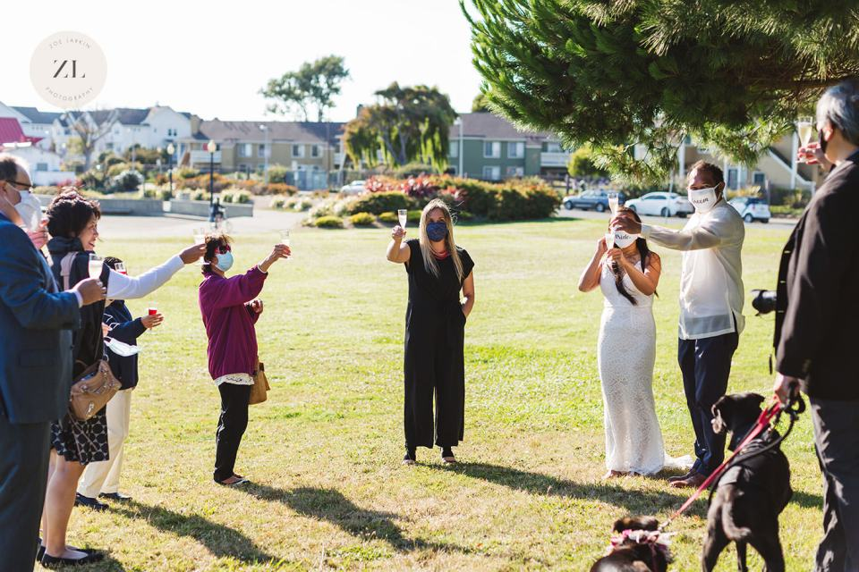 Saying 'cheers' with champagne at downsized wedding with socially-distanced wedding guests