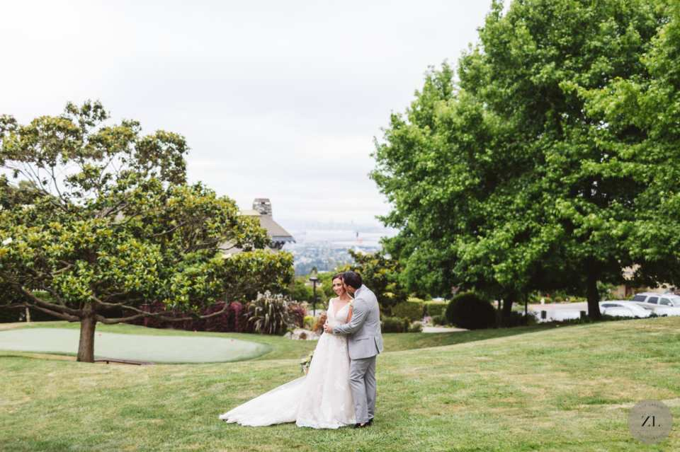 wide shot of bride and groom kissing on golf course at Country Club wedding