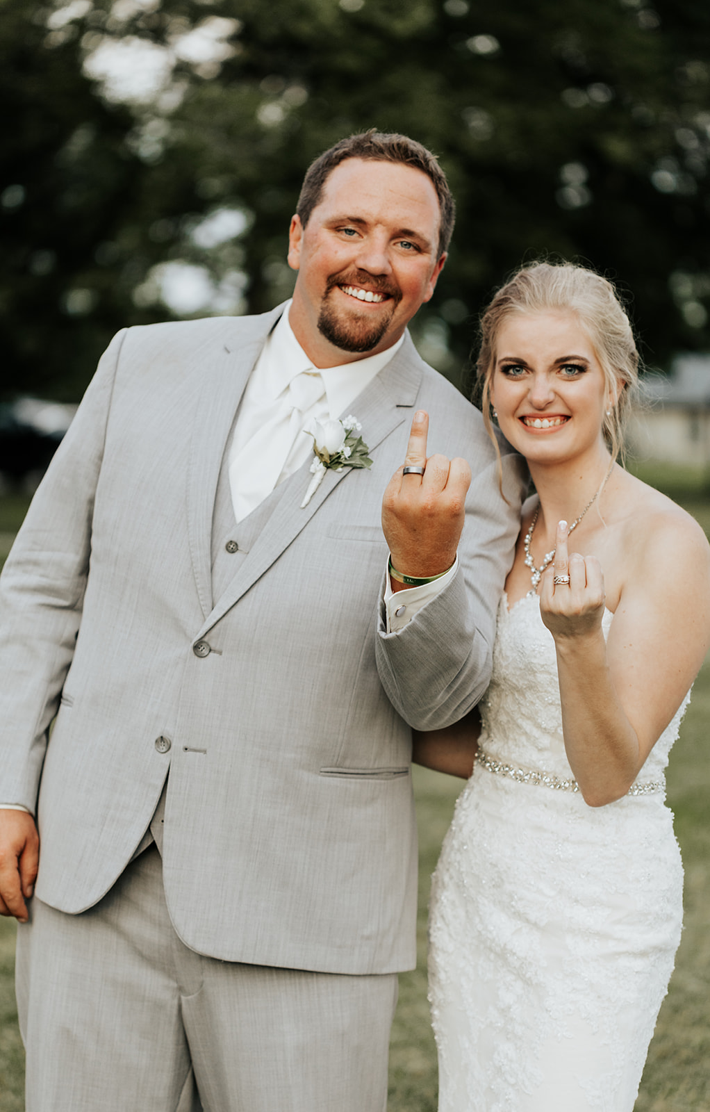 Sunny Wedding at Christian Conference Center in Newton Iowa flipping off the camera with wedding rings