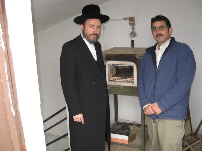 """עם הרב יצחק אנגלארד, בנו של האדמו""""ר האחרון מבית ראדזין, הממונה על צביעת התכלת מדיונון בימינו. התנור המשמש לשריפת בלוטות הדיו של הדיונון"""