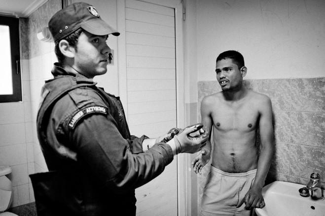 Ένας αστυνομικός ετοιμάζεται να πραγματοποιήσει σωματικό έλεγχο σε έναν Μπαγκλαντεσιανό, στην τουαλέτα του αστυνομικού τμήματος Ομονοίας.