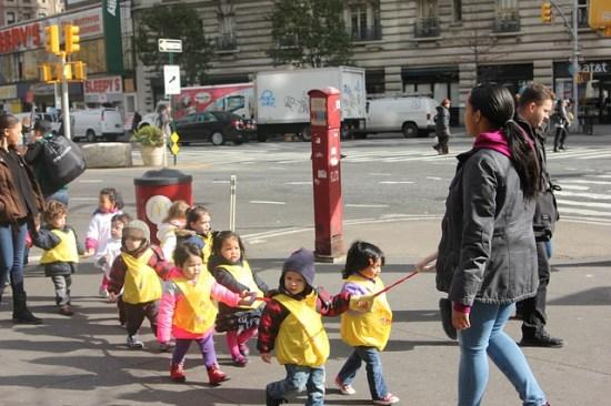 niños pequeños sujetos a una cuerda de excursión por la calle