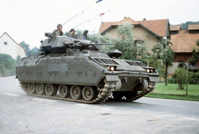 Un Vehículo de combate de caballería M-3A1 Bradley avanza por las cales de un pueblo alemán durante el ejercicio REFORGER 1985. Una de las características distinguibles de la versión de caballería del Bradley son sus troneras anuladas. Imagen: US Army.