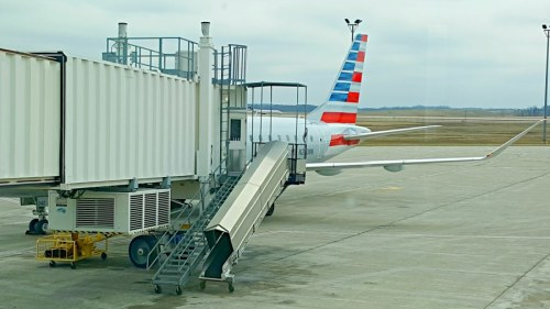 an airplane tail visible behind the extended catwalk, waiting to board my first fliht
