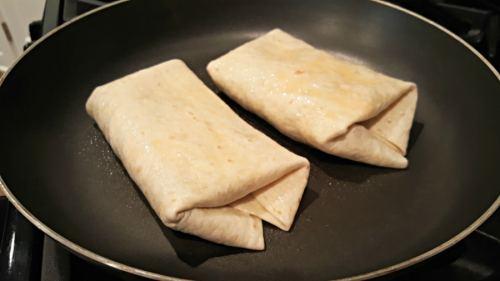 Crispy Chicken Chimichangas frying in a saute pan