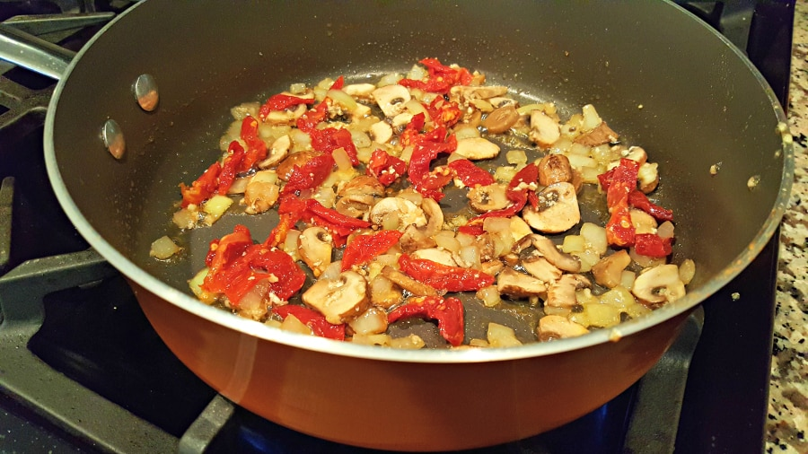 adding the tomatoes to the onions and mushrooms
