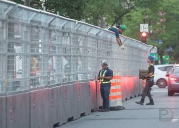 Des travailleurs s'affairent à installer la clôture de sécurité autour du circuit.