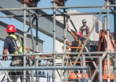 Des travailleurs assemblent une structure (une passerelle?) à côté du circuit.