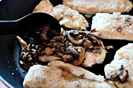 chicken with mushrooms and cheese step by step recipe with ingredients and pictures, spooning mushroom sauce over cooked chicken breast fillets in a large frying pan