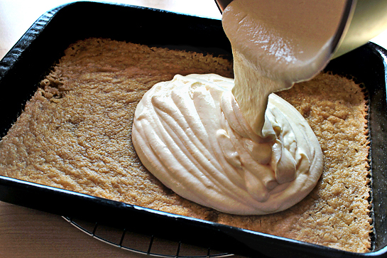 Caramel apple cheesecake cookie bars recipe with step by step pictures. Pouring cream cheese mixture over baked cookie batter.