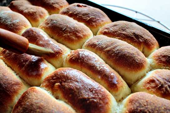 baked sweet jam filled buns out of the oven brush with warm milk and sugar