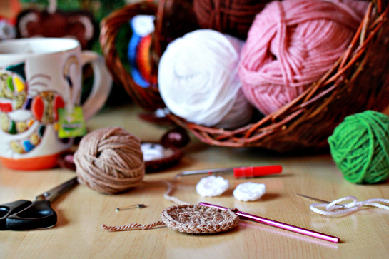 balls and skeins of yarn, crochet work, crochet hook, scissors, needle, and mug with tea on the table