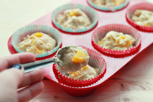 filling muffin liners with peach muffin batter in a muffin tin