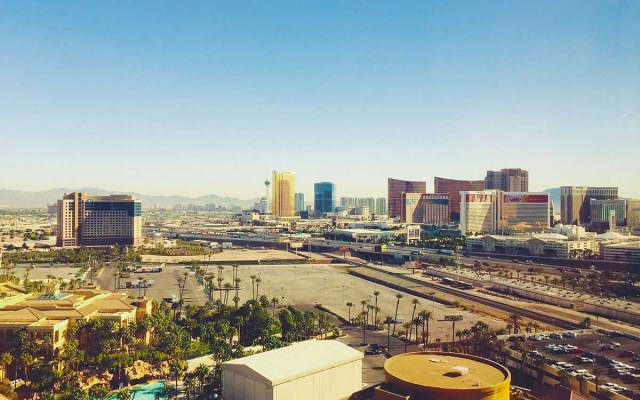 The Las Vegas cityscape sits atop the desert on a sunny day.