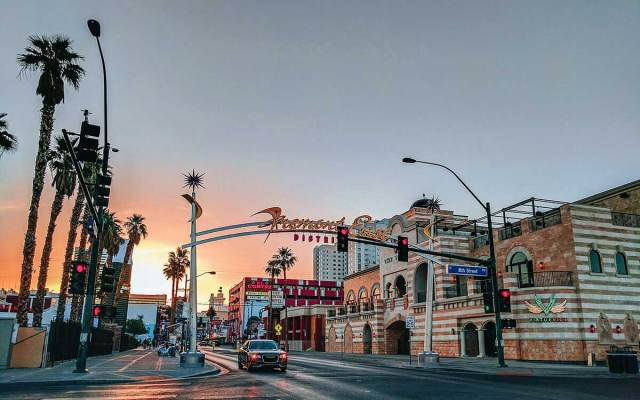 """A sign that reads, """"Fremont East District"""" arches above a Downtown Vegas city street."""