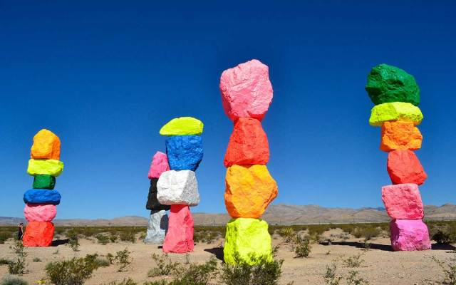 A colorful selection of stacked rocks titled Seven Magic Mountains, a Las Vegas landmark, sits atop the desert landscape.