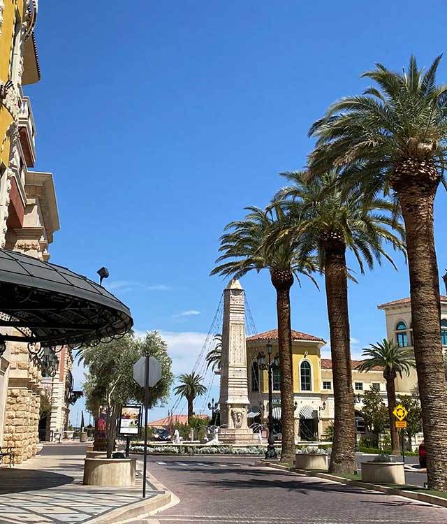 Palm trees and yellow buildings line a street at Tivoli Village in Las Vegas.