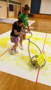 Using the Zot Art Art Roller, walking around the painting to leave her mark.