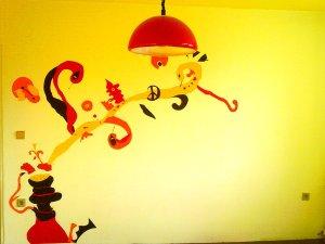 Fotografie stěny, na které je barevnýma tapetama nalepená vodní dýmka s psychedelickými tvary.