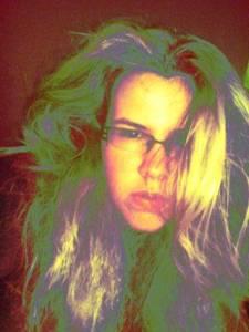 Fotografie Zrzavé holky s ještě světlou barvou vlasů, polovina obrovských hustých vlasů jí zakrývá dlouhý obličej.