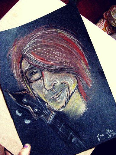 Portrét suchým pastelem na černém papíře - na obrázku je muž s výraznými rysy, červenými vlasy a černými brýlemi. Vedle něj stojí baskytara.