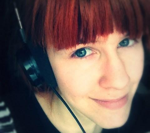 fotografie zrzavé holky bez brýlí, má na uších velká černá sluchátka.