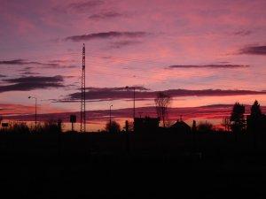 Tmavě fialovočervené nebe při západu slunce v prosinci se spoustou těžkých, černých mraků. Přes nebe se vinou černé linie pouličních lamp a stromů a domu.