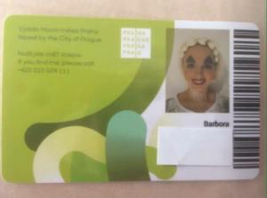 Zelenobílá lítačka s fotkou Barbory - má šílený makeup, obrovské modré stíny, strašně tlustě namalované obočí, vyjevený výraz, červenou rtěnku a kýčovité květy ve vlasech.