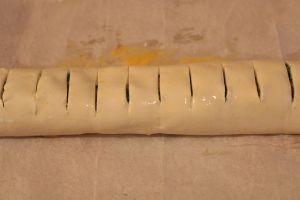 Blätterteigrolle einrollen einschneiden und mit Ei bepinseln
