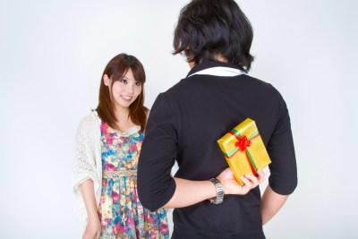 プレゼントを後ろで隠す男性と不思議そうに男性を見つめる女性